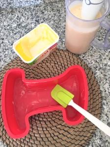 Untando el molde con mantequilla.
